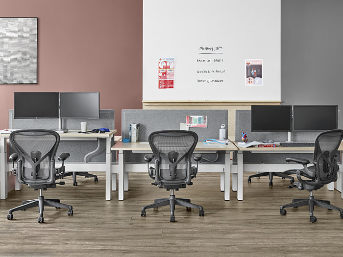 Well lit workspace with a two piece Renew Link and individual desk positioned against the wall with three Aeron chairs behind each work surface